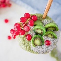 green matcha and chia pudding with baby kiwis and cranberries